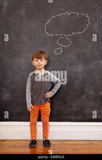 Niedlichen kleinen Jungen mit einer Gedankenblase an die Tafel. Voller Länge Schuss des jungen mit der Hand Stockbild