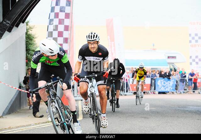 Amateur-Zyklus Bergrennen in einer Küstenstadt. Männlichen und Teenager Rennen gegeneinander in einem Stockbild