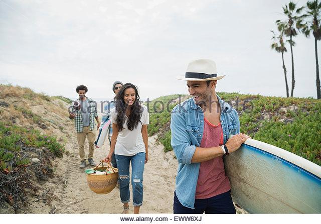 Freunde mit Surfbrett und Picknick Korb Strand Weg Stockbild