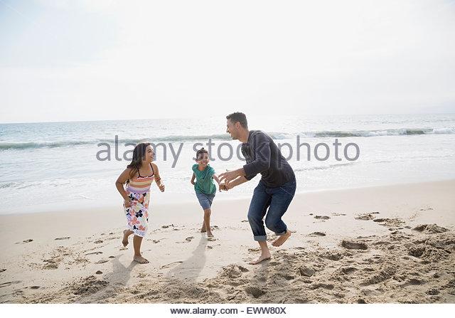 Spielerische Familie läuft am Sonnenstrand Stockbild