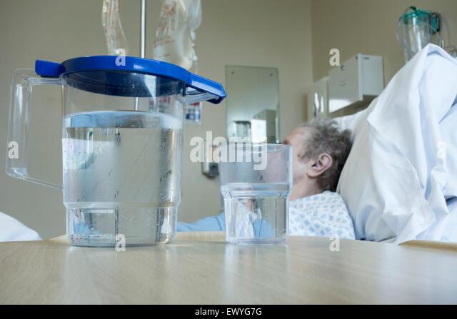 Ältere Dame in ihre neunziger Jahre im Bett auf NHS Krankenstation mit Krug Wasser auf den Nachttisch. Stockbild