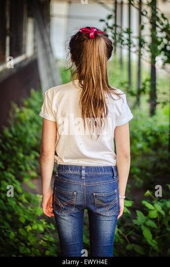 Ansicht von hinten von einem Mädchen in einem Garten steht Stockbild