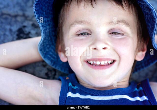 Draufsicht eines jungen, der mit seinen Händen hinter dem Kopf auf dem Boden liegend Stockbild