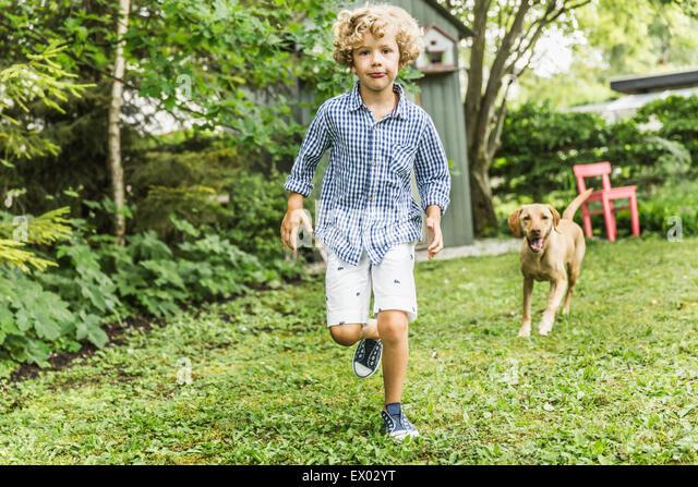 Junge mit Hund im Garten Stockbild
