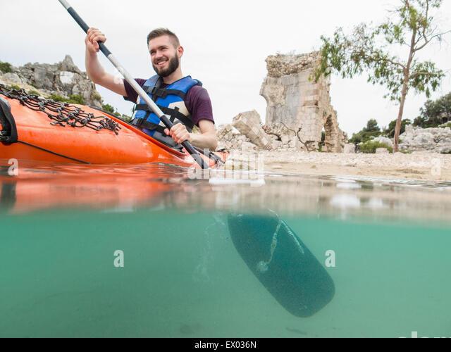 Mann, Kajakfahren in der Nähe von Ruinen, Lykischen Weg, Türkei Stockbild