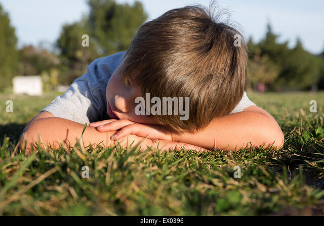 Mürrisch junge mit Kopf nach unten liegend auf Park Rasen Stockbild