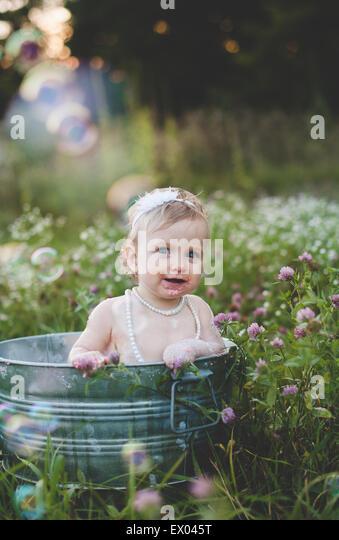 Porträt von Babymädchen Baden in einer Zinn Badewanne in eine Wildblumenwiese Stockbild