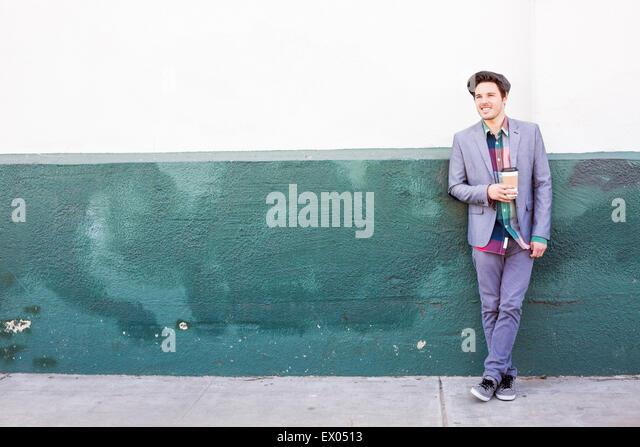 Junger Mann stehend von Mauer mit Kaffee Stockbild
