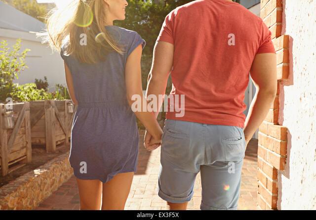 Rückansicht Schuss eines jungen Paares, die Hand in Hand spazieren draußen in ihrem Hinterhof. Zugeschnittene Stockbild