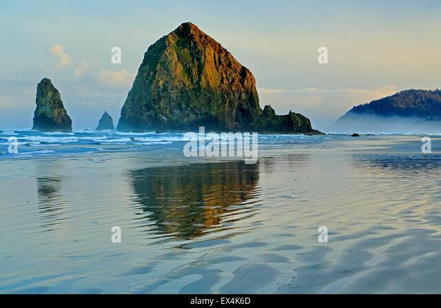 Haystack Rock wider auf Wasser und Wellen, Cannon Beach, Oregon USA - Stock-Bilder
