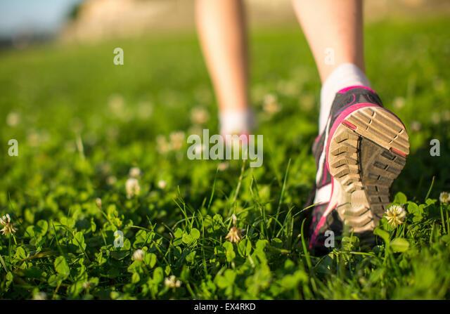 Wanderer zu Fuß in dem grünen Rasen im Freien, flachen Winkel Nahaufnahme des Fußes. Stockbild