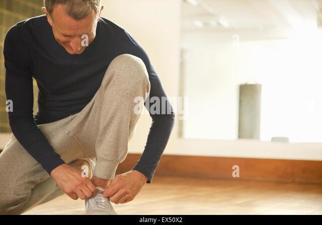 Reifen Sie Mann Übung Kleidung Schnürsenkel binden Stockbild