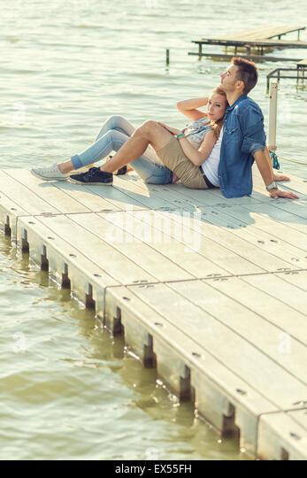 Paar in Liebe sitzen auf dem Pier, umarmen Stockbild