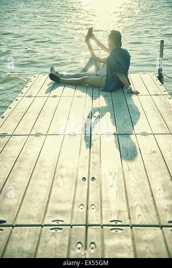 Paar in der Liebe, die sitzen auf dem Pier, selfie Stockbild