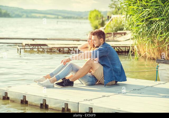 Paar in Liebe auf dem Pier, sitzen Stockbild