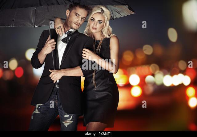 Intelligente Paare, die mit dem schwarzen Regenschirm Stockbild