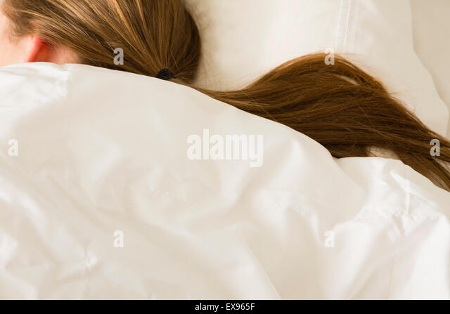Frau mit Pferdeschwanz in weiße Bettwäsche schlafen Stockbild