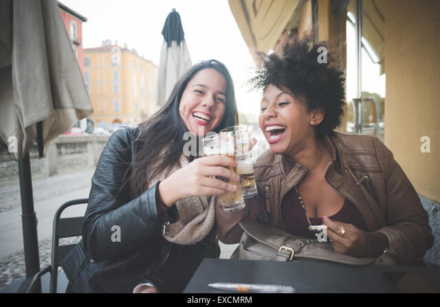 zwei multiethnischen schöne junge Frau Schwarz und kaukasischen Spaß trinken ein Bier in der Stadt Stockbild