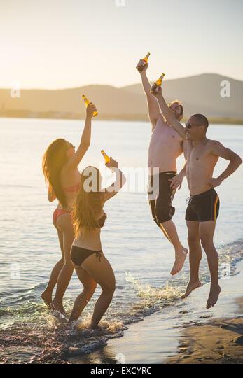 Gruppe von multiethnischen Jugendliche Frauen und Männer am Strand im Sommer trinken Bier springen und tanzen Stockbild