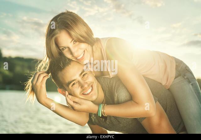 Paar in Liebe umarmen am See, Sonne flare Stockbild