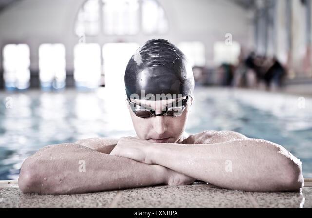 Schwimmer im Hallenbad am Beckenrand Stockbild