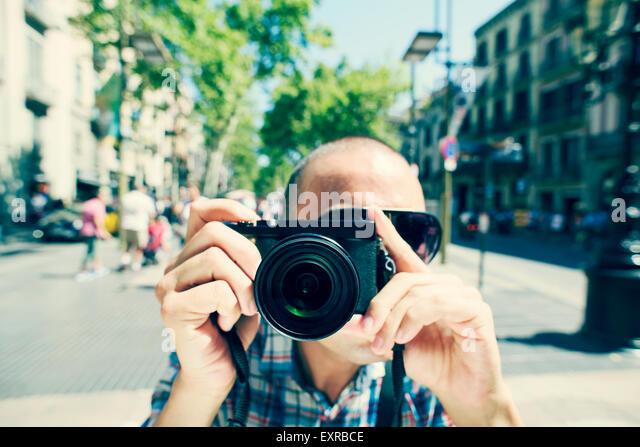 ein junger kaukasischer Mann mit Sonnenbrille zeigt seine Kamera auf den Betrachter auf La Rambla in Barcelona, Stockbild