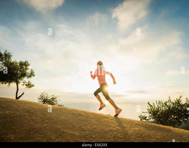 Frau läuft in Bergen Stockbild