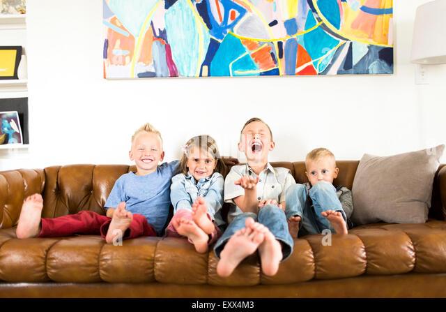 Lächelnde Kinder (2-3, 4-5, 6-7) auf Sofa sitzen Stockbild