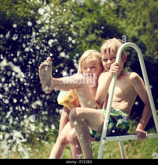 Kaukasische Kinder - Jungen und Mädchen spielen in der Nähe von Schwimmbad, Spritzwasser Stockbild