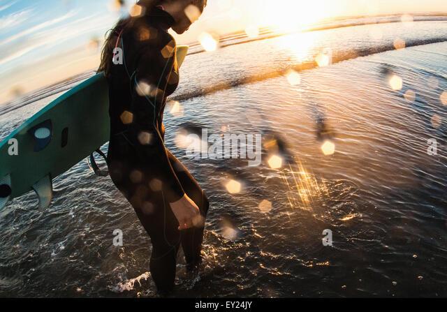 Weibliche Surfer Paddeln im Meer bei Sonnenuntergang, Cardiff-By-The-Sea, Kalifornien, USA Stockbild