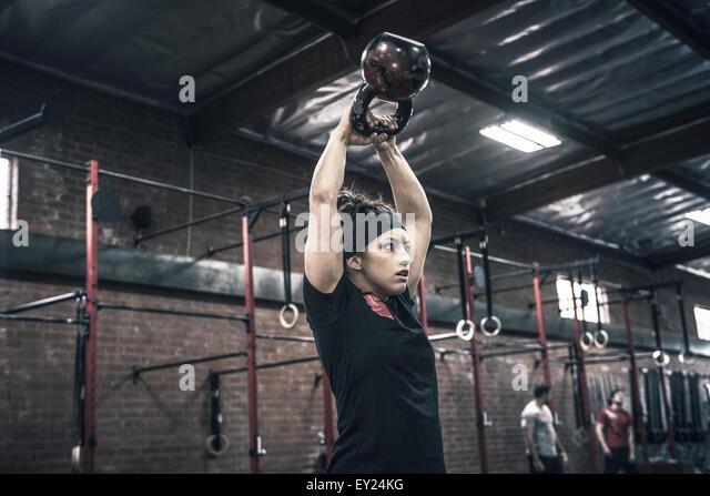 Junge Frau hält Wasserkocher Glocken im Fitness-Studio Stockbild
