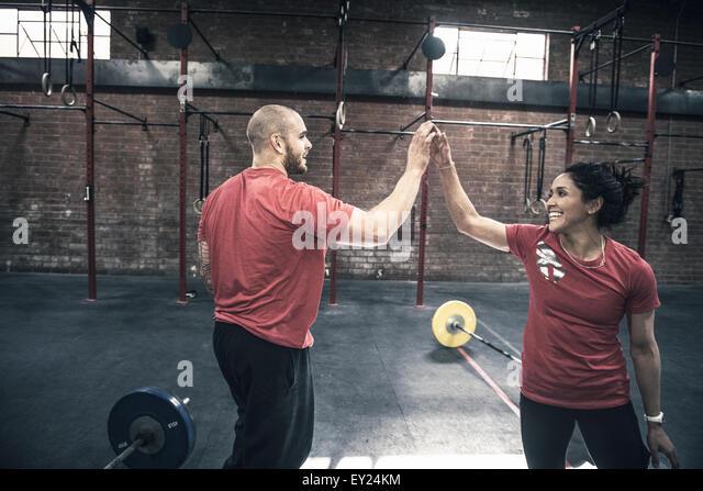 Junger Mann und Frau geben einander hoch fünf in gym Stockbild