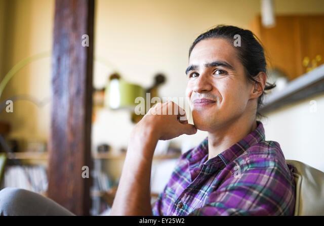Porträt des jungen Mannes sitzen drinnen relaxen Stockbild