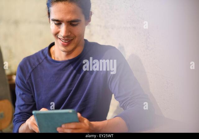 Junger Mann mit digital-Tablette, drinnen Stockbild