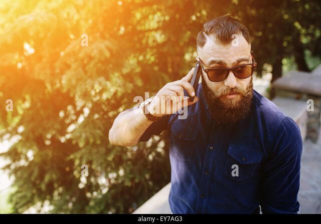 bärtige spricht per Telefon Stockbild
