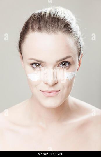Junge Frau mit Streifen von Lotion auf Gesicht Stockbild