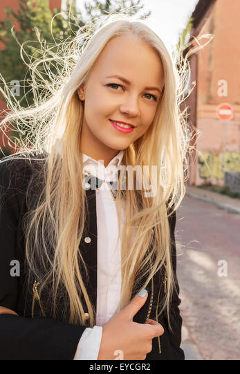 blonde Frau, die in der Altstadt lächelnd am sonnigen Tag Stockbild