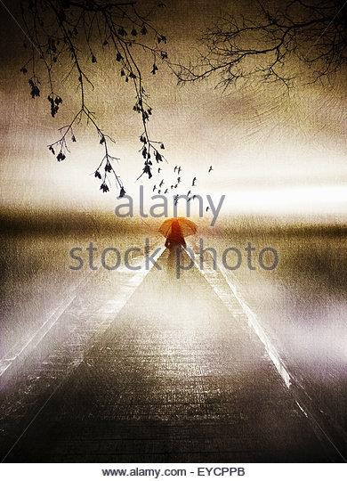 Einsame Frau mit roten Regenschirm auf atmosphärische Steg Stockbild