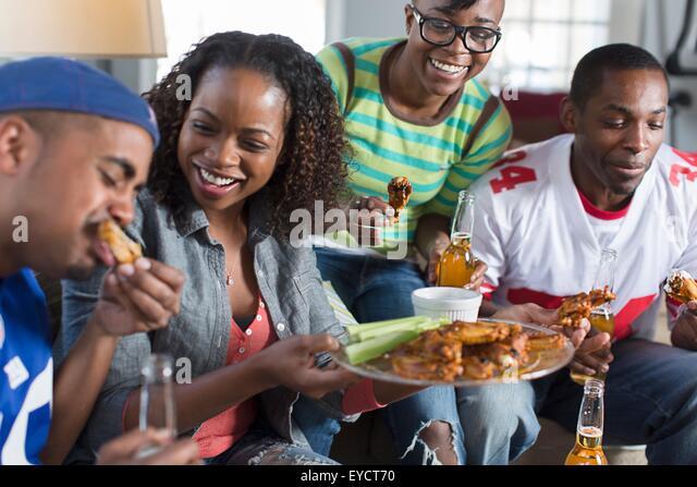 Gruppe von Erwachsenen Freunden Essen zum mitnehmen auf Sofa im Wohnzimmer Stockbild