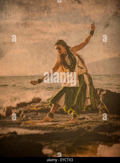 Imagegewinn der Frau Hula tanzen auf Küstenfelsen tragen Tracht, Maui, Hawaii, USA Stockbild