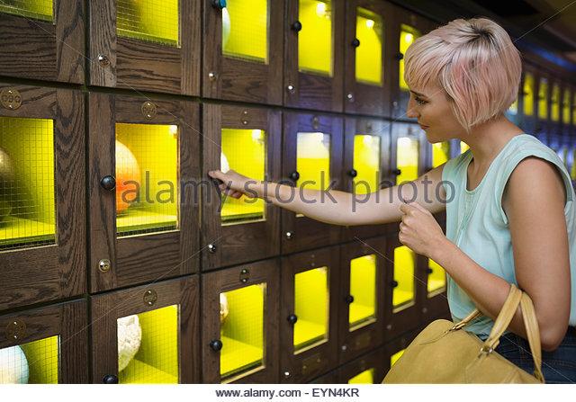 Junge Frau, die Bowling-Kugel Schließfach zu öffnen Stockbild