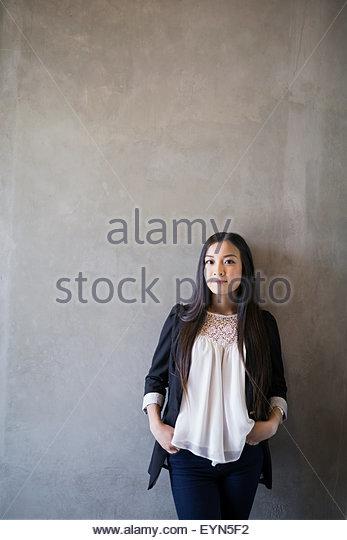 Selbstbewusste Frau Porträt Hände in den Taschen grauen Hintergrund Stockbild