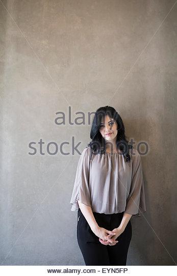 Porträt, selbstbewusste Frau mit Händen umklammert grauen Hintergrund Stockbild
