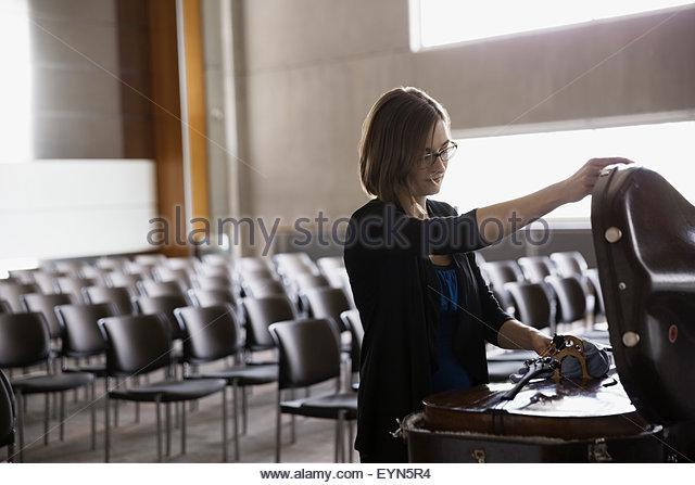 Weibliche Cellist öffnen Cellokasten im auditorium Stockbild