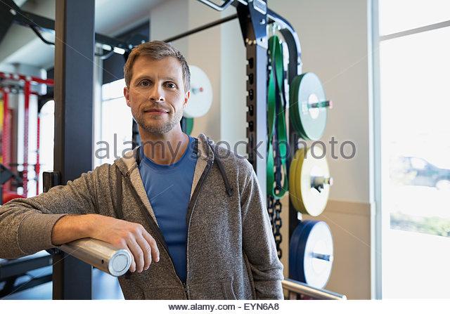 Portrait Mann stützte sich auf Trainingsgeräten im Fitnessstudio Stockbild