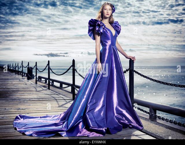 Junge Frau trägt ein schönes langes blaues Abendkleid steht im Waterfront, künstlerische Mode Porträt Stockbild