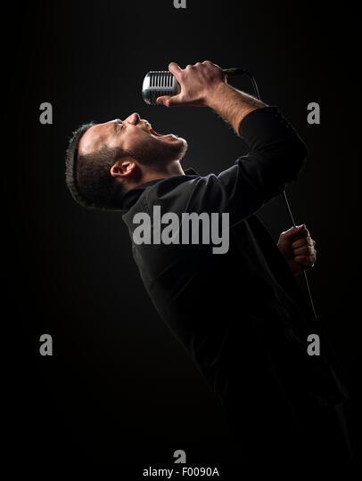 Sänger mit Mikrofon vor einem dunklen Hintergrund Stockbild