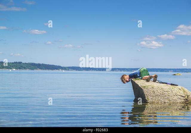 Junge auf einem Felsen blickte auf sein Spiegelbild im Meer Stockbild
