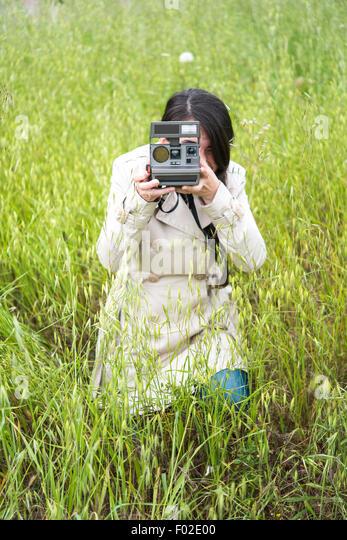 Frau, die ein Foto mit einem Vintage Sofortbild-Kamera Stockbild