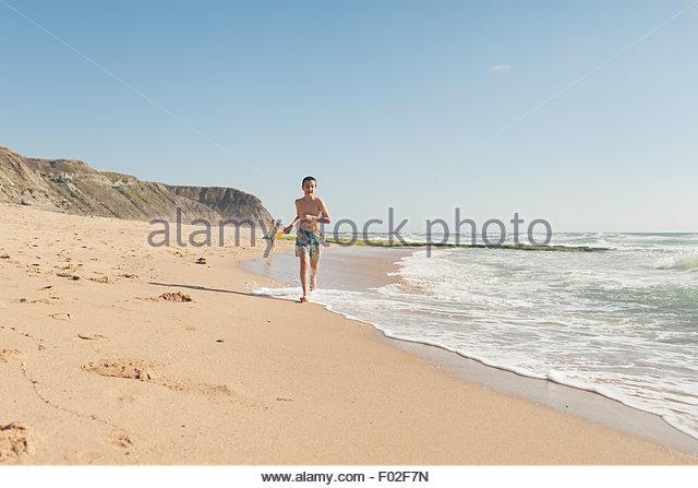 Zwei Jungs Rennen am Strand, Lissabon, Portugal Stockbild
